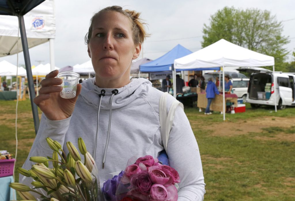 Caitlin Mance of Watertown, Mass., tastes Norumbega hard cider at the Brunswick market. Maine's new law allows makers to offer samples of their alcoholic beverages at farmers markets, which have begun in earnest with the onset of warmer weather.