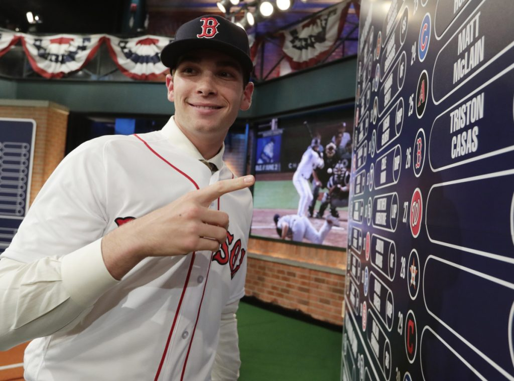 Triston Casas, 18, poses at the overall draft board Monday night after being selected in the first round of the major league draft by the Boston Red Sox with the 26th pick.