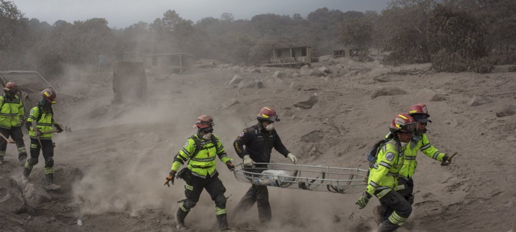 "Rescue workers run for cover as the Volcan de Fuego, or ""Volcano of Fire,"" blows more clouds of ash in the El Rodeo hamlet of Escuintla, Guatemala, Tuesday. Officials fear the number of dead was sure to climb."