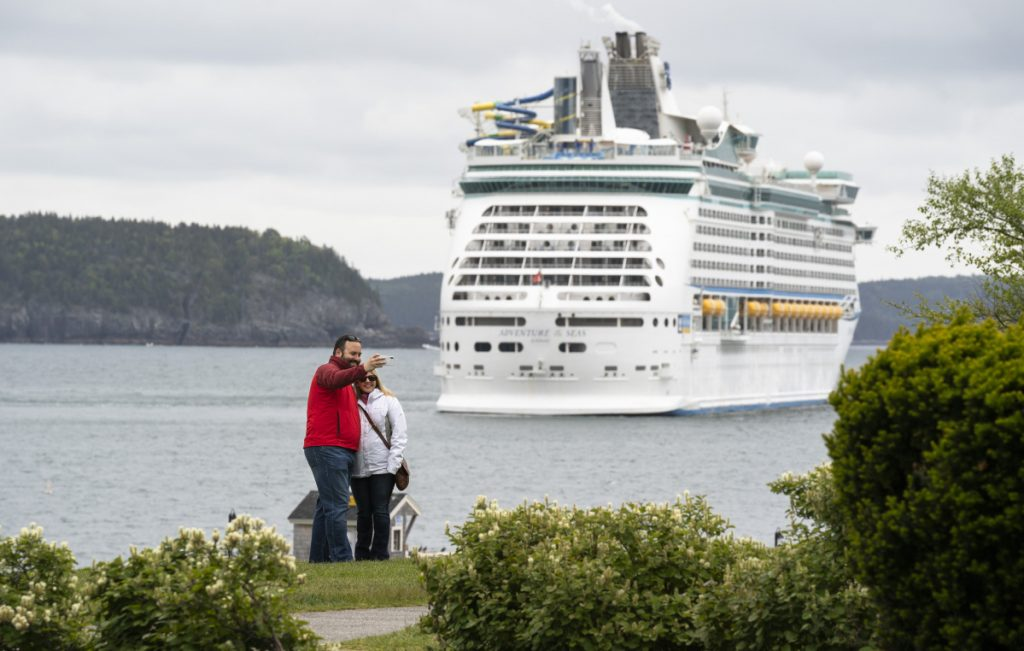 The Adventure of the Seas provides the backdrop for a couple snapping a self-portrait last week in Agamont Park along Bar Harbor's waterfront. The town expects 230,000 cruise ship passengers to visit this year and residents are struggling with how to accommodate that crush of people and the corresponding traffic snarls caused by tour buses. Residents will vote Tuesday on the purchase of a state-owned ferry terminal north of town.