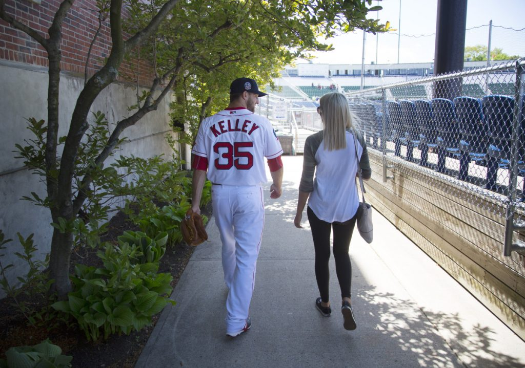 "Portland Sea Dogs pitcher Trevor Kelley walks with his wife, Jamie, at Hadlock Field in Portland. With long hours and wages that amount to slightly more than Maine's minimum wage, playing in the minors is a challenge, Kelley says. ""You just have to grind through it,"" he says. ""It's more the opportunity. That's the way I think about it."""