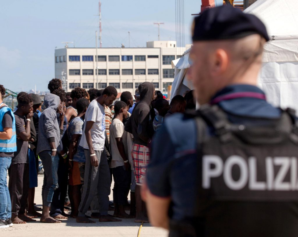 Migrants line up after disembarking at the Reggio Calabria harbor in southern Italy on Saturday. Meanwhile, an aid ship carrying 629 migrants rescued in the Mediterranean was waiting to learn where it can dock.