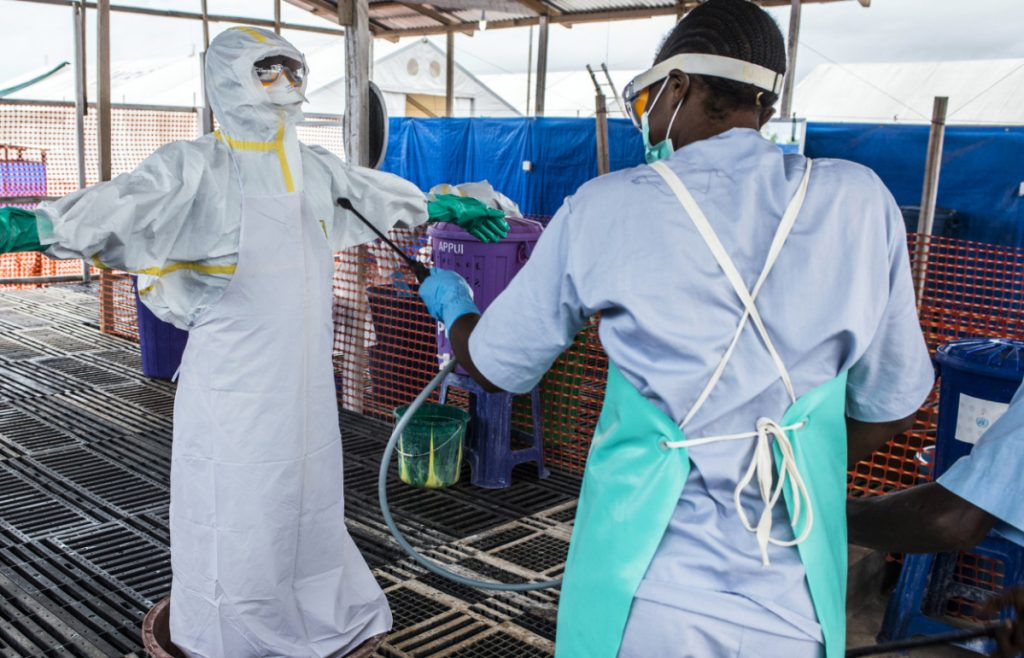 A healthcare worker cleans a colleague wearing Personal Protective Equipment at an Ebola Treatment Center in Coyah, Guinea, on Sept. 10, 2015.  MUST CREDIT: Bloomberg photo by Waldo Swiegers