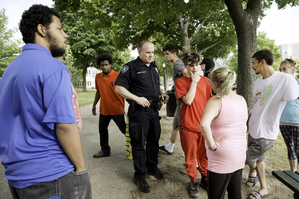 Lewiston police officer Tom Murphy talks with people Wednesday about a fight in Kennedy Park Tuesday night.