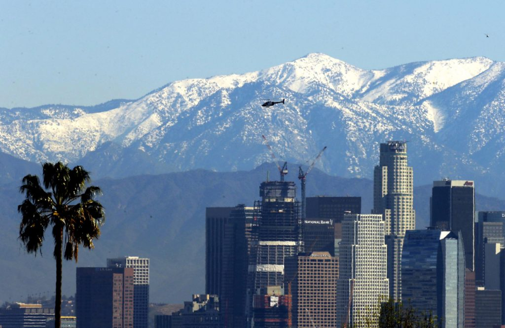 California voters will be asked this November if they want to split the state into three separate states: Northern California, which would include San Francisco, left; California, which would include Los Angeles, pictured in front of the snow-capped San Gabriel Mountains; and Southern California, which would get San Diego, seen here enveloped in smoke from a wildfire.