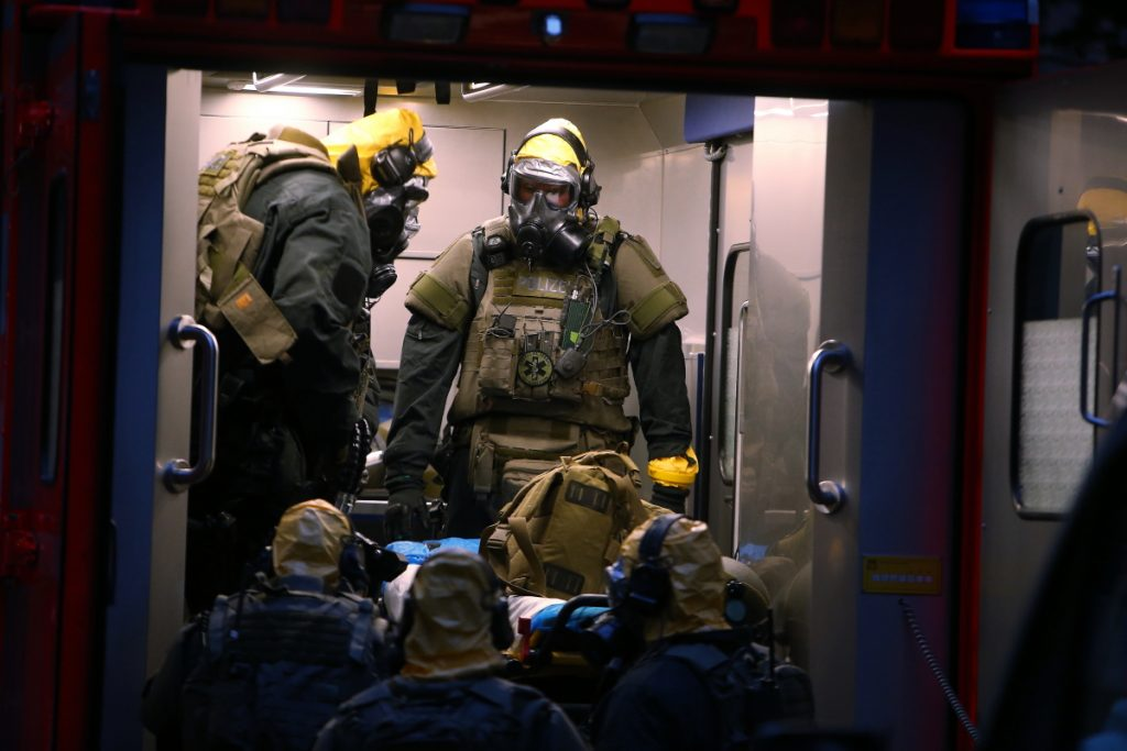 German police officers in protective gear enter a rescue car during an operation to search an apartment in Cologne, Germany, late Tuesday.