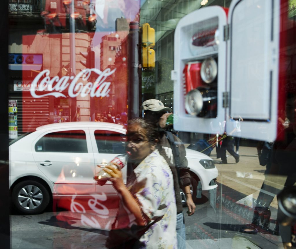 A woman is reflected in a Coca-Cola store window display as she drinks a Coke in Mexico City. In the southern city of Ciudad Altamirano, a store owner says a drug gang has seized control of soda distribution and raised prices.