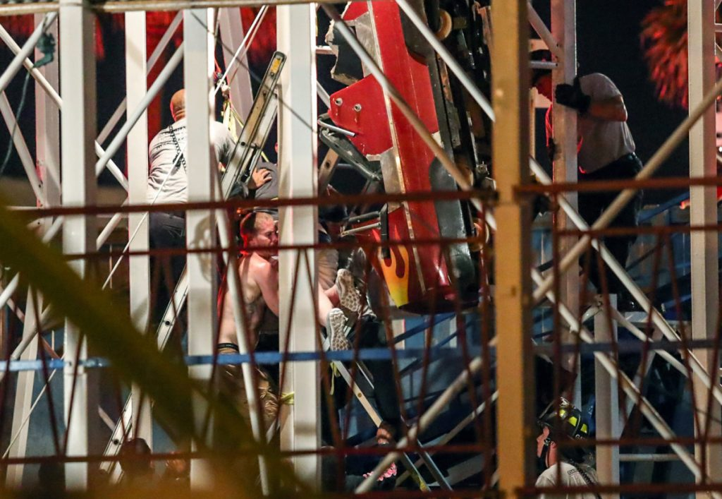 Daytona Beach Fire Department personnel rescue riders from a roller coaster car that derailed.