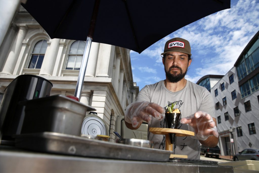 Jordan Rubin, owner of Mr. Tuna Mobile Sushi Bar, prepares a spicy scallop and crab handroll at the corner of Commercial and Custom House streets.