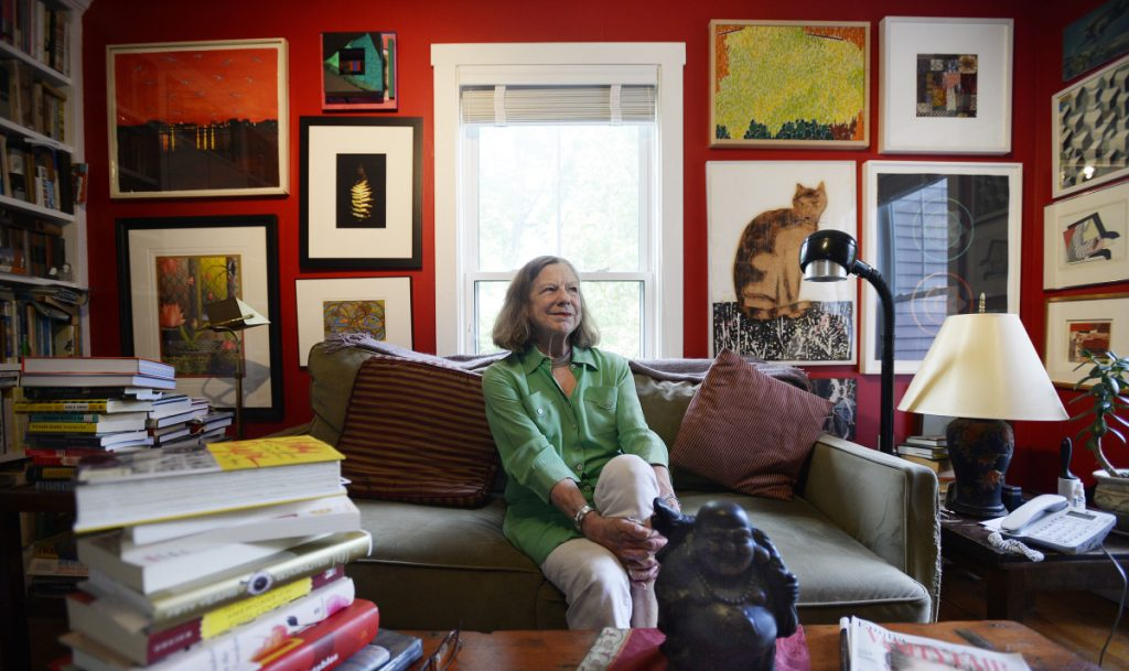 "Anne Zill, who recently retired as art director of the Art Gallery at UNE in Portland, sits in the library of her Portland home Thursday. ""I see my life as ... one great adventure after another,"" she said."