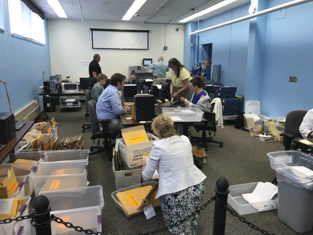 Workers in the Maine Secretary of State's Office return Monday to the task of scanning and downloading voter ballots ahead of a ranked-choice calculation on Tuesday.