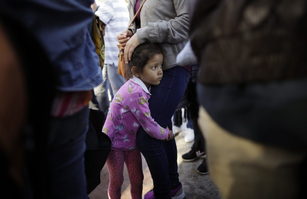 Nicole Hernandez holds onto her mother June 13 as they wait with others in Tijuana, Mexico, to request political asylum in the U.S. On the Senate floor Monday, independent Maine Sen. Angus King said the White House created the family separation policy and could easily end it.