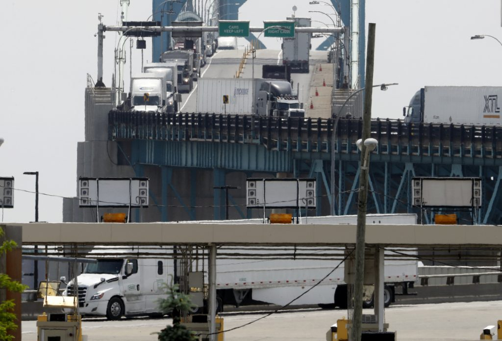 Trucks cross the Ambassador Bridge from Windsor, Ontario, into Detroit. In nearly a quarter-century since NAFTA was approved, a complex chain of auto parts makers has sprung up on both sides of the border.