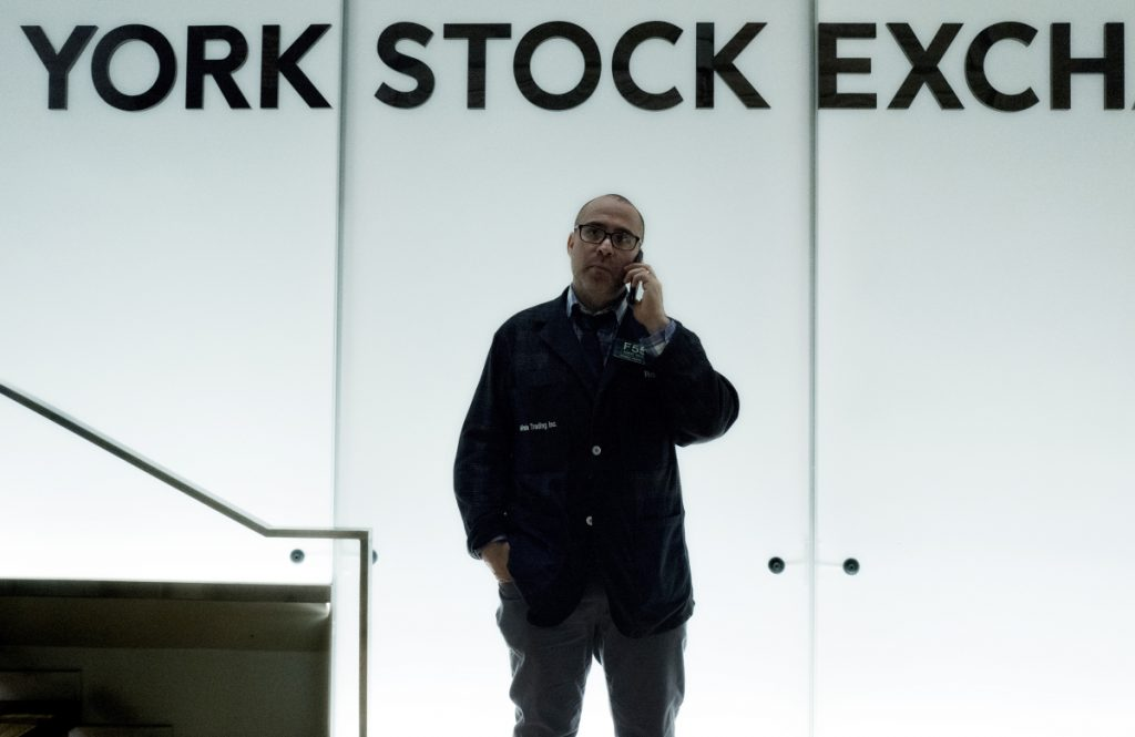 A trader talks on his phone before the start of trading Monday at the New York Stock Exchange.