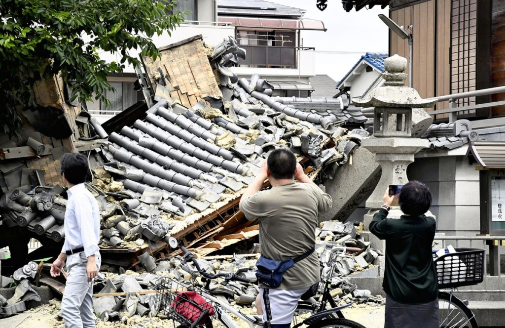 Residents photograph a temple gate in Ibaraki, Osaka Prefecture, that collapsed during the strong earthquake that hit western Japan shortly before 8 a.m. on Monday.