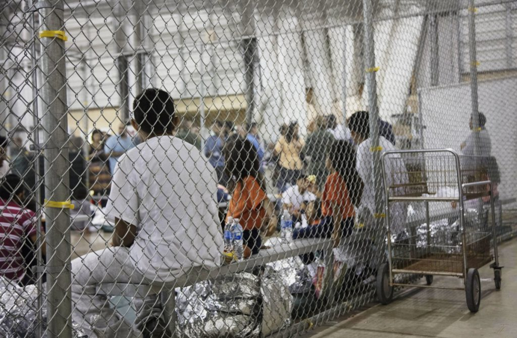 People who have been taken into custody, related to cases of illegal entry into the United States, sit in one of the cages at a facility in McAllen, Texas, on Sunday. Several states are now recalling or refusing to send National Guard troops to the border because of the Trump administration policy of separating children and parents.