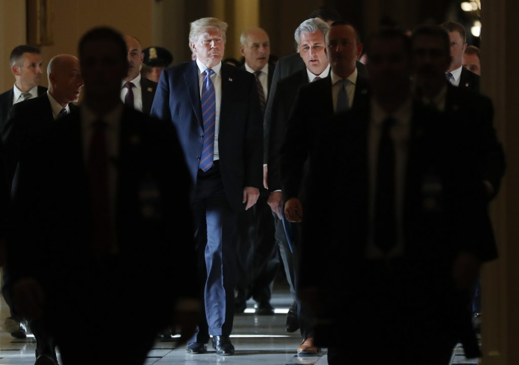 President Trump walks with House Majority Leader Kevin McCarthy of California as he leaves the Capitol after meeting with Republican leadership on Tuesday. Walking behind them is White House Chief of Staff John Kelly.