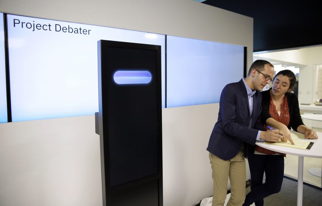 Champion debaters Dan Zafrir, left, and Noa Ovadia, right, prepare their arguments against the IBM Project Debater, at left, on Monday in San Francisco. The demonstration aimed to show that computers are getting better at responding to human language and speech.