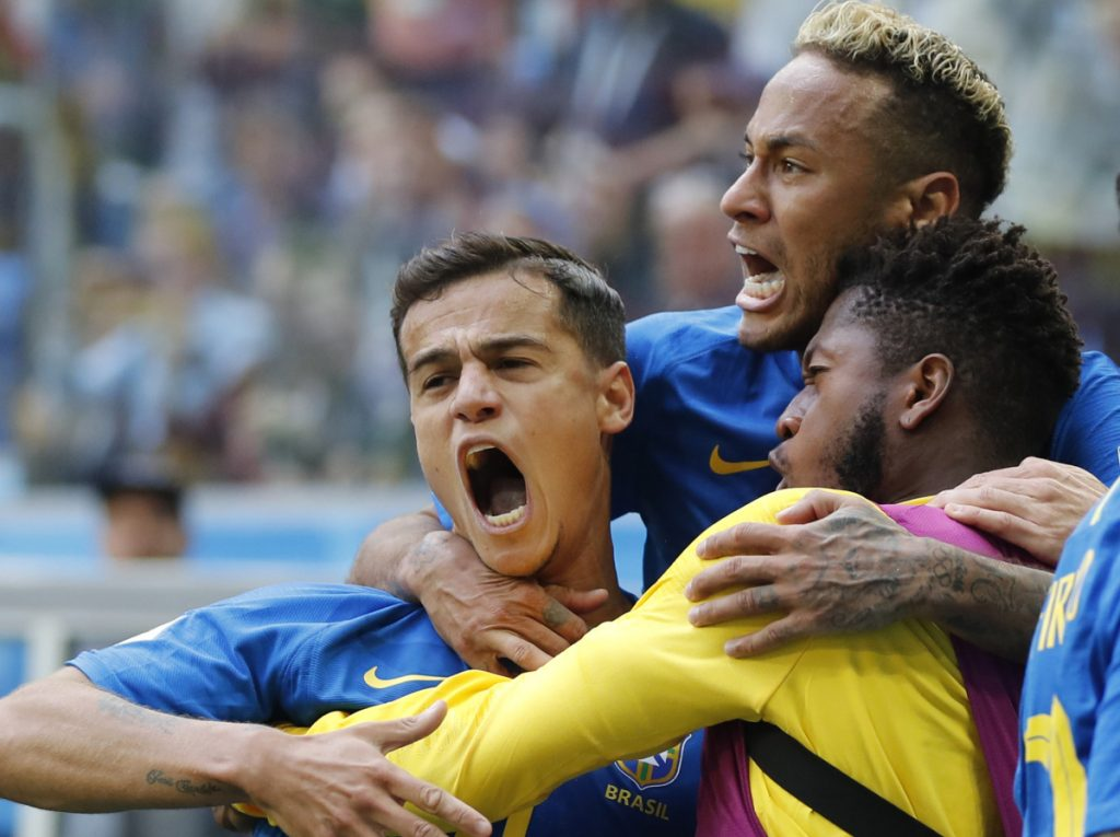 Brazil's Philippe Coutinho, left, celebrates scoring in the first minute of stoppage time with Neymar, top, and teammates during Friday's 2-0 win over Costa Rica in St. Petersburg, Russia.