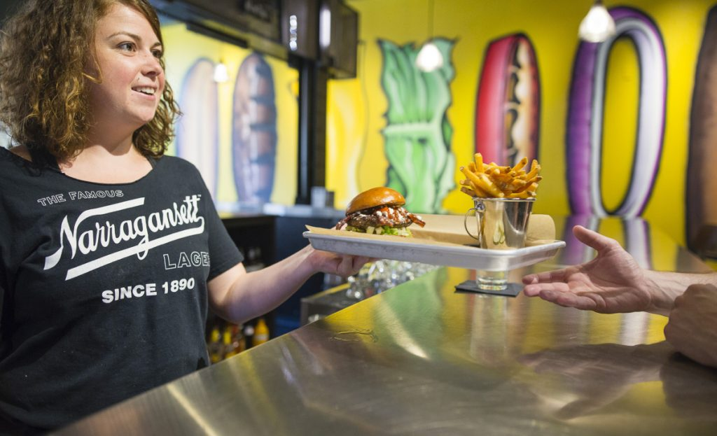 Server Maya Doyle delivers fries and a burger – with bacon, barbecue sauce and feta cheese – to Garrett Jones of Portland on Friday at BRGR Bar on Brown Street in Portland.