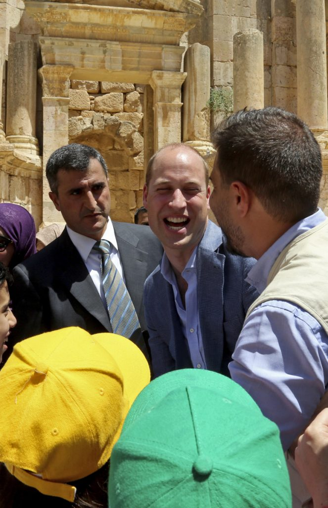 Britain's Prince William, center, laughs with a group of young people at an archaeological site in Jerash, northern Jordan, Monday.