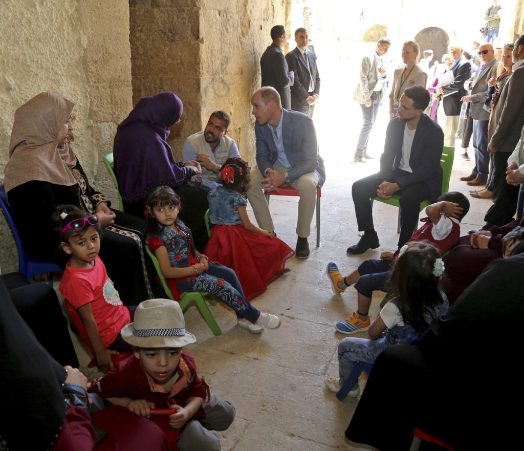 Prince William, center left, and Jordanian Crown Prince Hussain, center right, meet with people from an education and support program for Syrian and Jordanian children.