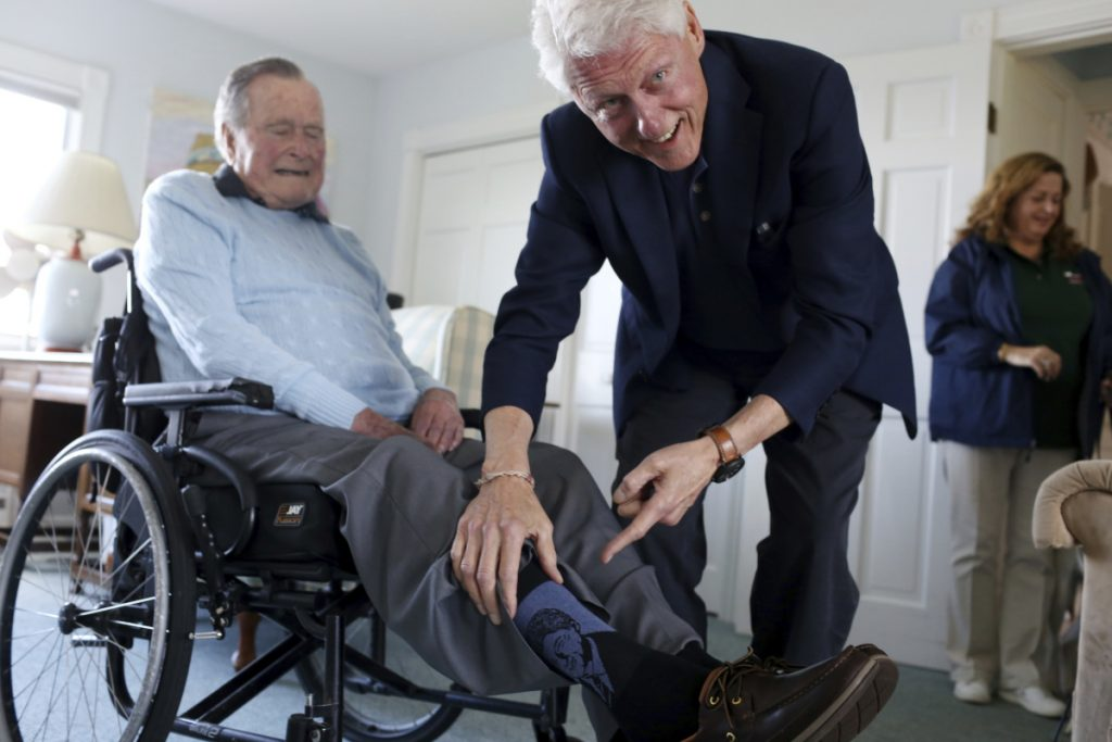 """Former Democratic President Bill Clinton jokes with former Republican President George H.W. Bush as Bush shows off a pair of """"Bill Clinton socks,"""" while Clinton visits Bush at his home in Kennebunkport on Monday."""