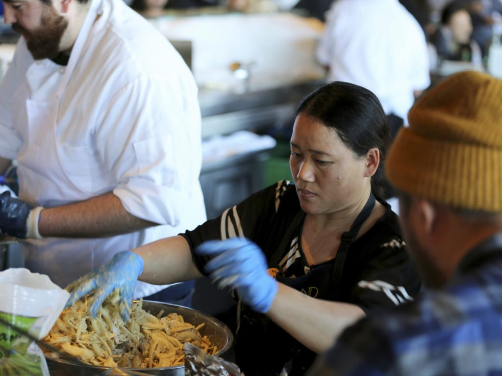 Pa Wah, a refugee from Myanmar, mixes shrimp in a turmeric tempura batter at the Hog Island Oyster Co. restaurant during the Refugee Food Festival.