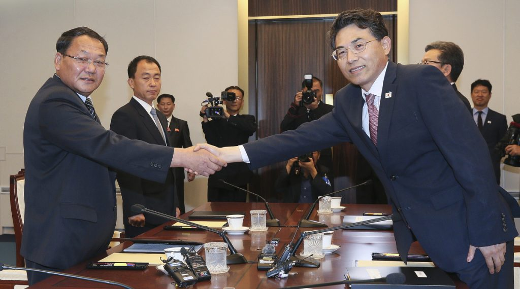 North Korean Vice Railroad Minister Kim Yun Hyok, left, shakes hands with his South Korean counterpart Vice Transport Minister Kim Jeong-ryeol during a meeting to discuss inter-Korean cooperation on railway upgrades. The meeting was held inside the Peace House at the border village of Panmunjom, South Korea, on Tuesday. (Korea Pool via AP)