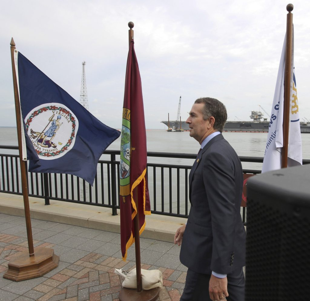 Gov. Ralph Northam walks to the podium Tuesday at a park in Newport News, Va., to discuss the state's support for Newport News Shipbuilding's hiring initiative. He said the state will help recruit and train workers.