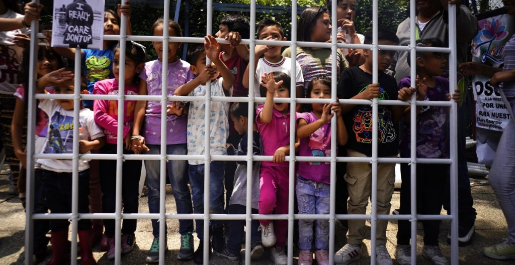 Children hold up a metal fence in Mexico City on Tuesday to protest immigrant children being detained by U.S. immigration authorities. The protest was organized by Lorena Osorio, independent candidate for Mexico City mayor ahead of July 1 elections.