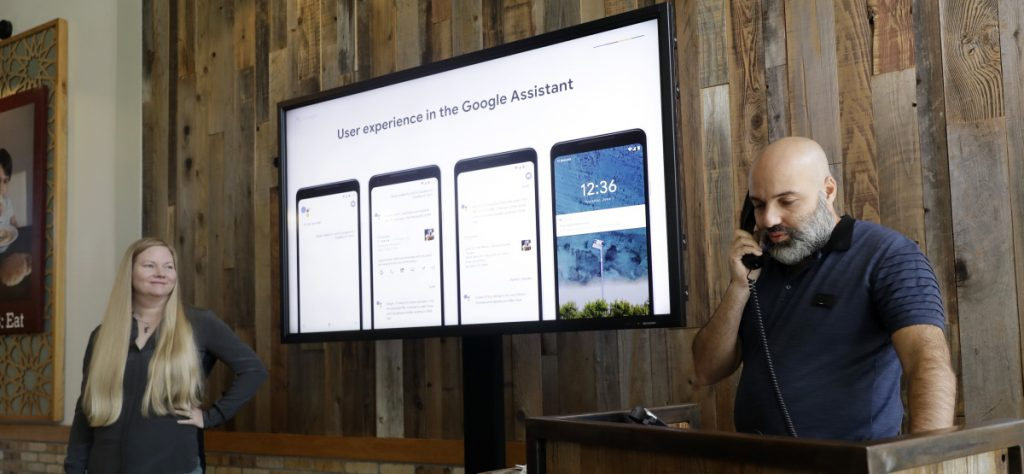 "Oren Dobronsky, right, owner of Oren's Hummus in Mountain View, Calif., demonstrates the Duplex program that will book an appointment over the phone, alongside Valerie Nygaard, product manager for Google. ""I think it will just bring more business,"" Dobronsky said."
