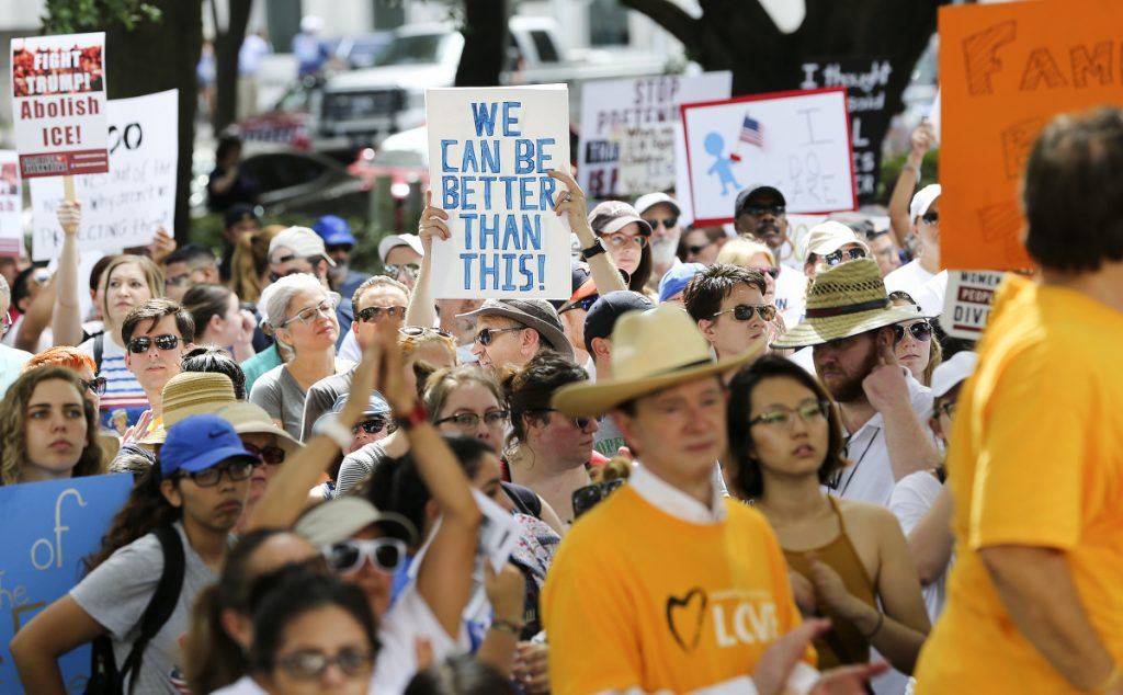 "Protestors hold signs during an immigration rally in Houston that started at City Hall and ended at U.S. Sen. Ted Cruz's office on Saturday, June 30, 2018 in Houston. Rallies were held across the nation calling on federal agencies to reunite families separated at the border under Trump's ""zero tolerance"" policy, as well as calling for the abolishment of ICE."