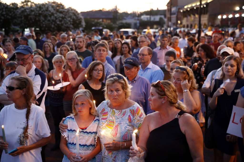Mourners stand in silence during a vigil in response to a shooting at the Capital Gazette newsroom, Friday in Annapolis, Md. Prosecutors say 38-year-old Jarrod W. Ramos opened fire Thursday in the newsroom.