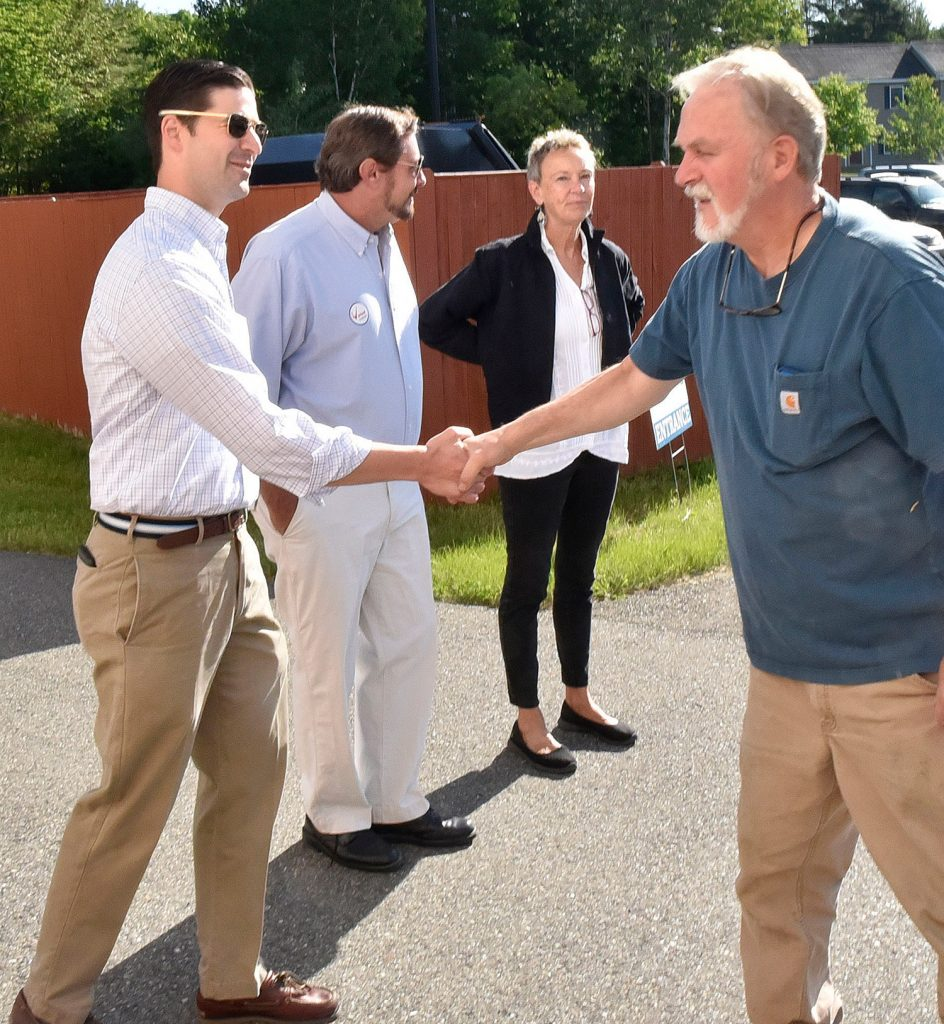"Waterville resident Brad Sherwood, right, shakes hands with Waterville Mayor Nick Isgro during early voting at Thomas College on Tuesday. Isgro is the subject of a recall effort spearheaded by former mayor Karen Heck at right. Candidate Mark Andre' is in center. Upon meeting Isgro in line, Heck said to him, "" Good luck today Nick, you're going to need it."""