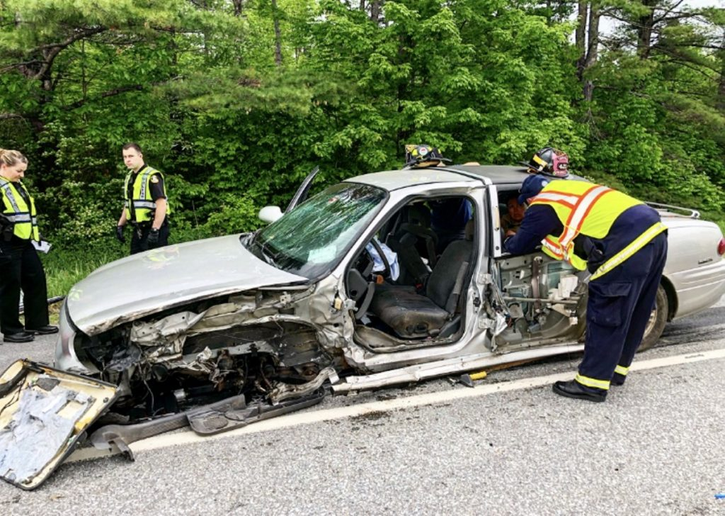 Law enforcement and rescue personnel inspect a mangled 2002 Buick LeSabre following a collision with a tractor-trailer Friday morning on Skowhegan Road in Fairfield. The vehicle's owner, John Hamlin, 64, of Cornville, was driving toward Fairfield when police say he got a flat tire, causing him to cross the center line and strike the tractor-trailer.
