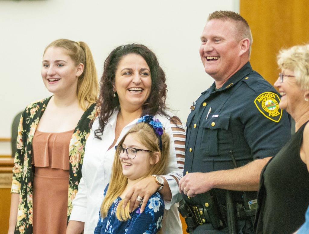 New Augusta Police Chief Jared Mills stands with family before being sworn in on Friday in the council chamber in Augusta City Center. From left, his daughter Jieselle Mills, wife Vivian Mills, daughter Jasmine Mills, Chief Jared Mills and his mother, Tish Begin.