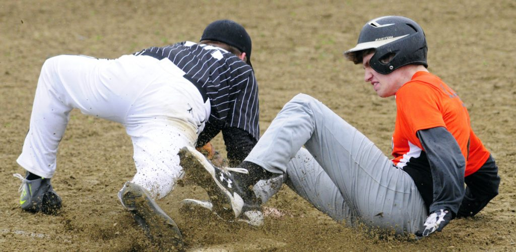 Staff photo by Joe Phelan   Lincoln Academy third baseman Basel White collides with Gardiner baserunner Cole Lawrence during a Kennebec Valley Athletic Conference Class B game at Hoch Field in Gardiner.