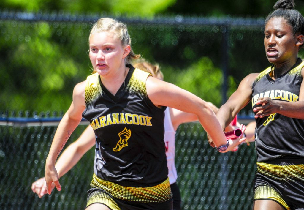 Staff photo by Joe Phelan   Maranacook's Grace Despres, left, takes the baton from Kiana Gordon in the 4x100 meter relay during the Class C track and field meet Saturday in Waterboro.