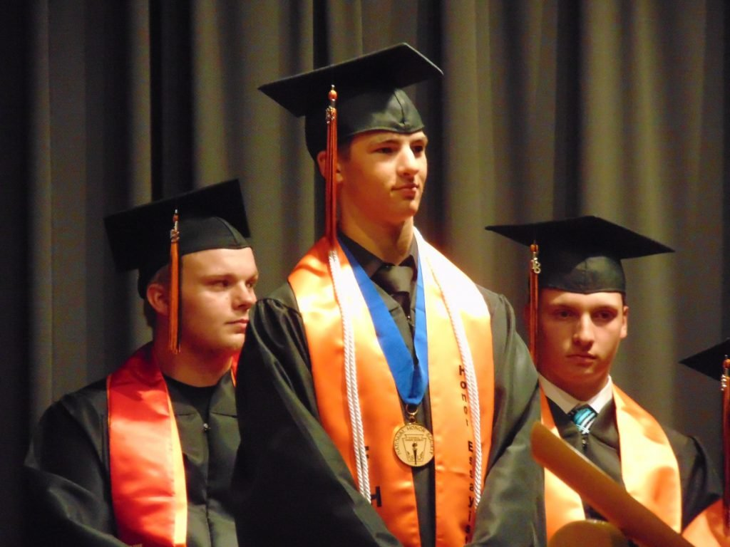 Forest Hills class of 2018 Honor Essayist, Carson Veilleux, stands as he is recognized by a fellow graduate during Saturday's ceremony in Jackman. Veilleux also spoke during the ceremony, warning his classmates against the pull toward their generation's culture of instant gratification.