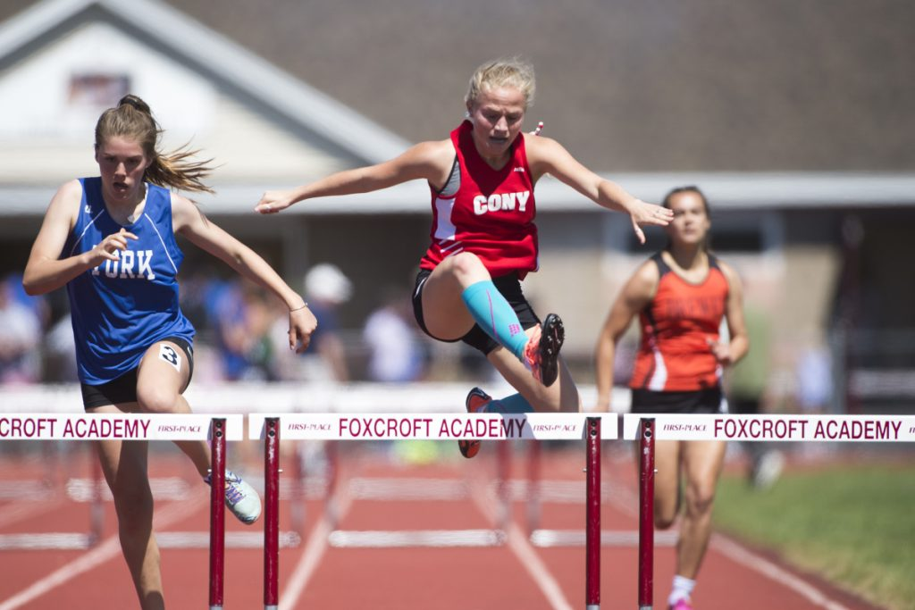 Staff photo by Michael G. Seamans   Cony's Anna Reny competes in the 300 meter hurdle at the Class B track and field state championships Saturday at Foxcroft Academy.