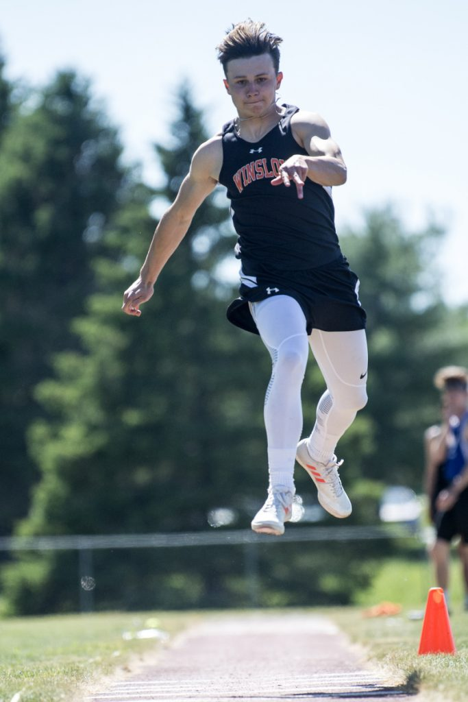 Staff photo by Michael G. Seamans   Winslow's Jake Warn competes in the triple jump at the Class B track and field state championships Saturday at Foxcroft Academy.
