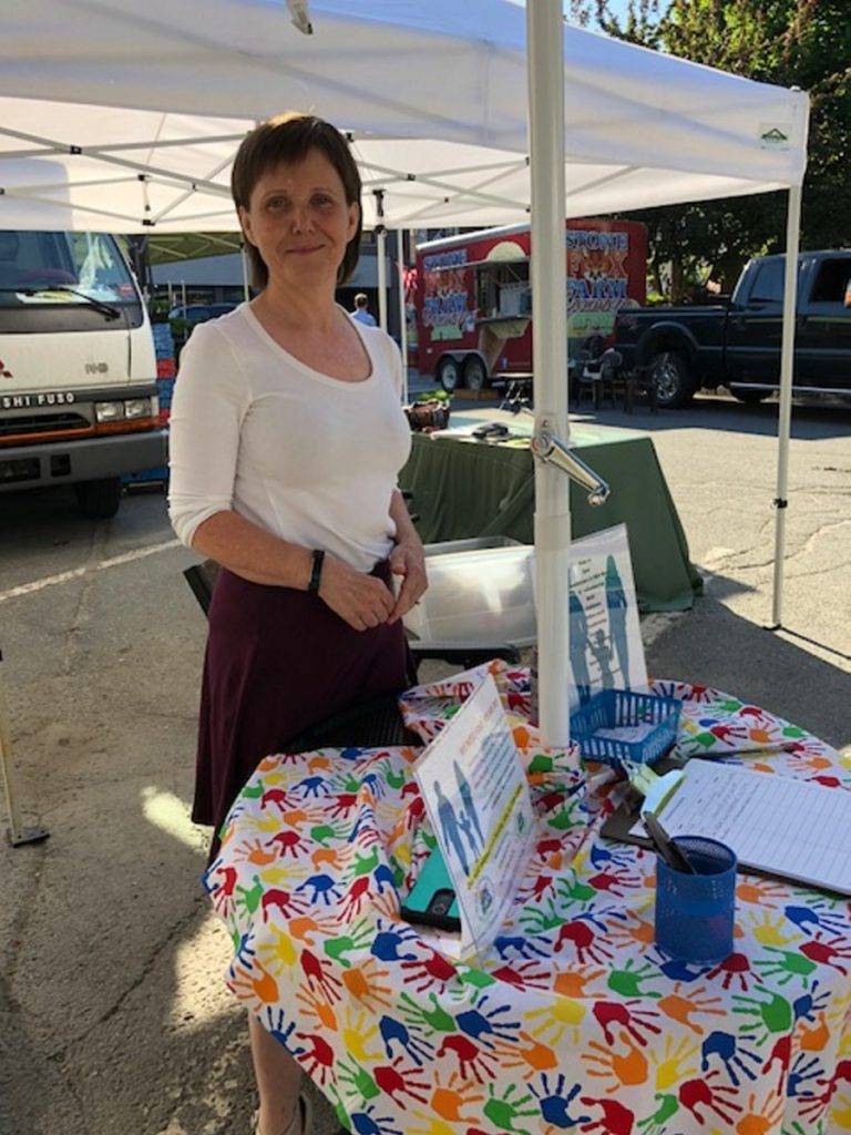Elizabeth LaBua sets up a small table under an umbrella at the Downtown Waterville Farmers Market on Thursday to give people an opportunity to make a difference. She recruits volunteers to work at the homeless shelter.