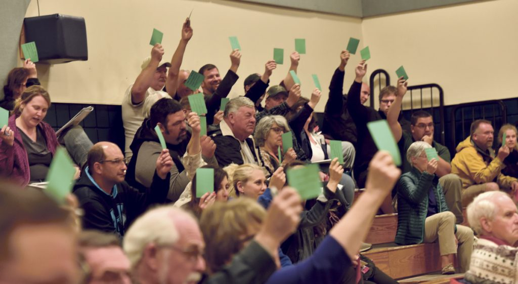 Vassalboro residents vote on an article Monday during the Vassalboro Town Meeting.