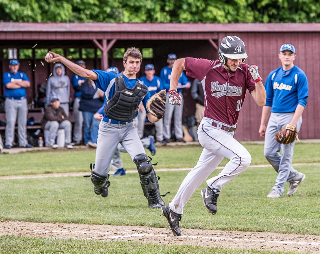 Monmouth Academy's Devon Poisson sprints to first base as Mt. Abram catcher Ben Debias throws the ball to first base during Tuesday's Class C South prelim game in Monmouth.