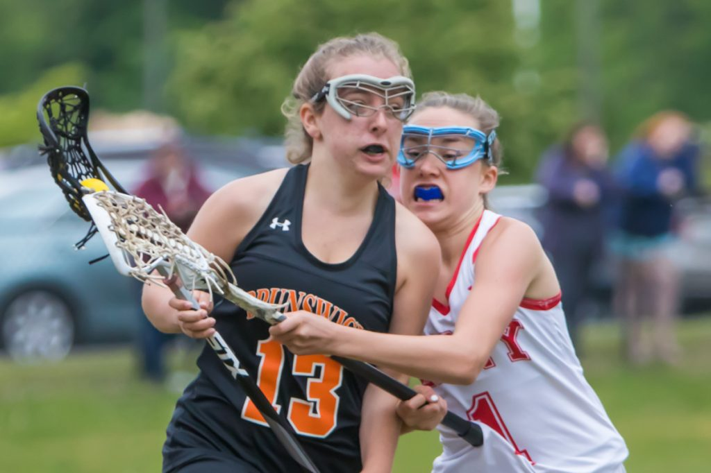 Brunswick's Lila Solberg, left, carries the ball while Cony defender Sierra Clark tries to knock her stick during a Class B lacrosse prelim Wednesday at Cony High School.