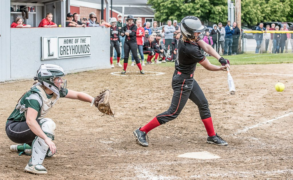Lisbon's Ivy Morris connected for a key hit in the sixth inning in front of Carrabec catcher Bailey Dunphy during a Class C South quarterfinal game Wednesday in Lisbon.