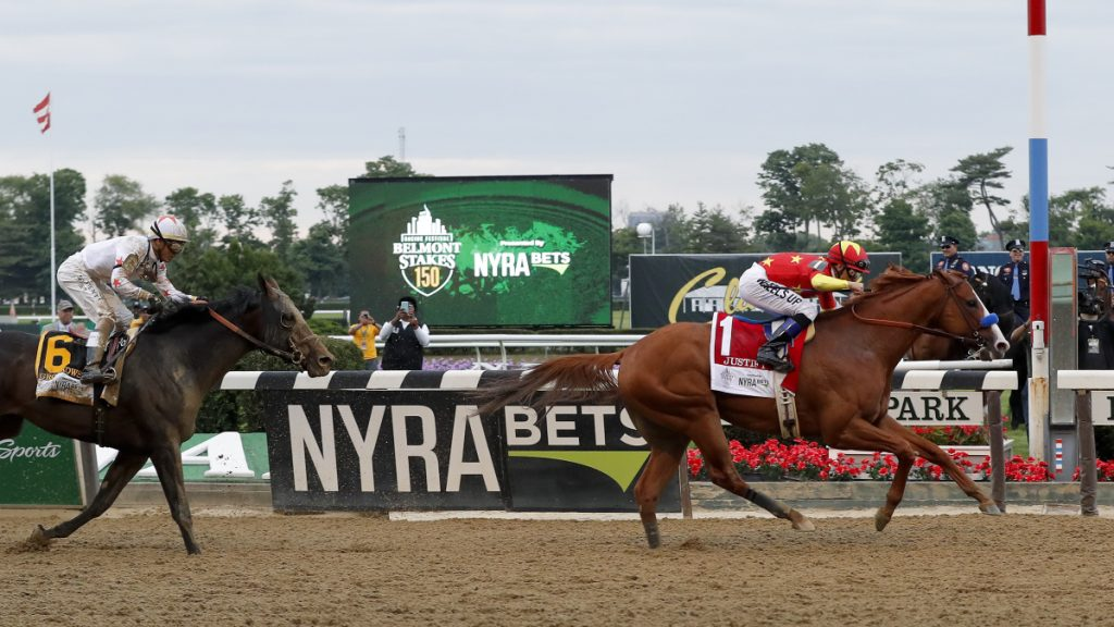 Justify crosses the finish line ahead of Gronkowski to win the 150th running of the Belmont Stakes and the Triple Crown on Saturday in Elmont, New York.