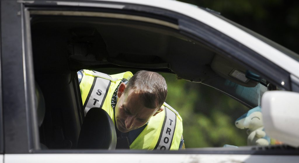 Maine State Police Sgt. Patrick Hood inspects a vehicle involved in a crash on Route 17 in Chelsea on Monday.