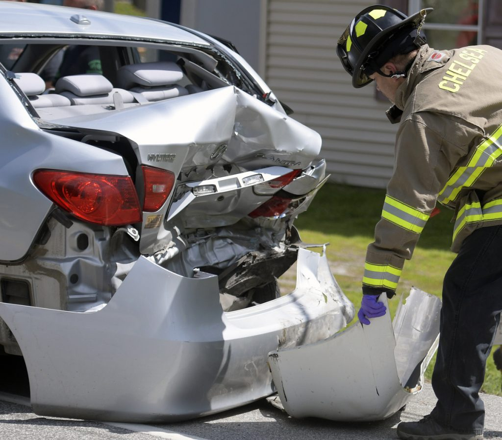 Firefighters collect debris from a two-car crash on Route 17 in Chelsea on Monday.